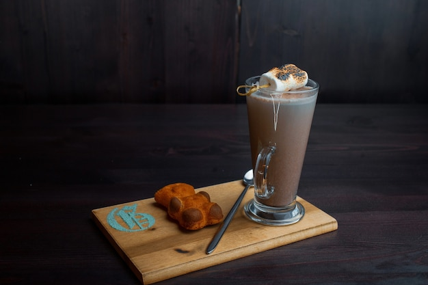 Hot sweet tasty latte in a transparent glass with biscuit decorated with aerial marshmallow on a wooden board in a cafe