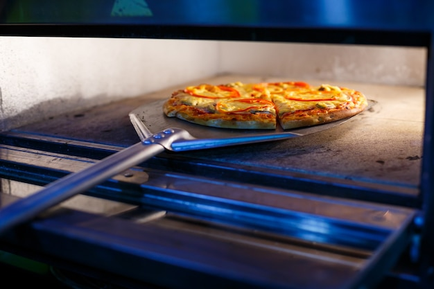 金属製のシャベルに厚い皮が付いたトマトチーズと肉を使った、ホットでおいしいアメリカンピザ