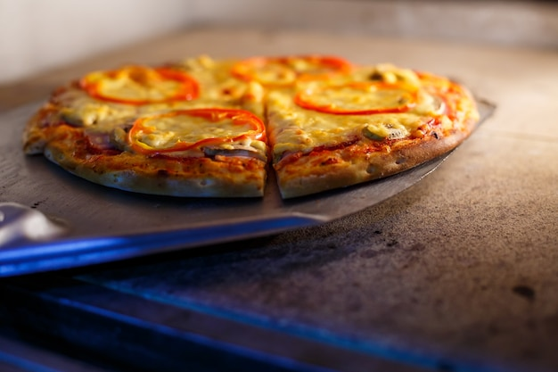 Hot tasty american pizza with tomato cheese and meat with a thick crust on a metal shovel, the baker takes out the pizza from the oven