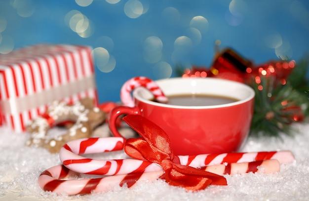 青い背景の上のクリスマスキャンディーと赤いカップのホットおいしい飲み物