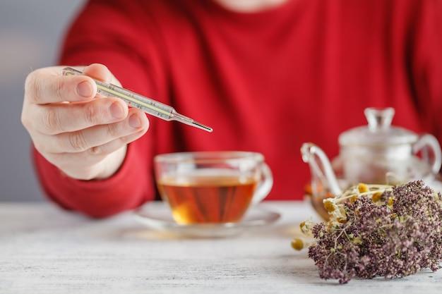 熱に対して熱いお茶。男性は温度計の温度を見て、蜂蜜とハーブティーを飲む