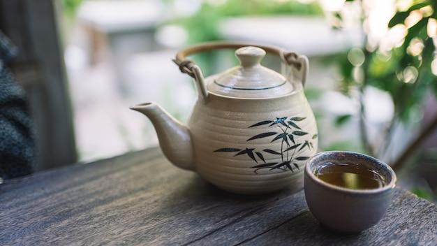 植物を背景にした木製のテーブルに熱いお茶とやかん