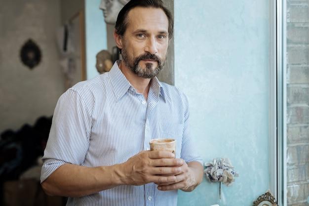 温かいお茶。熱いお茶でカップを保持しながら窓の近くに立って飲むひげを生やした成熟した男