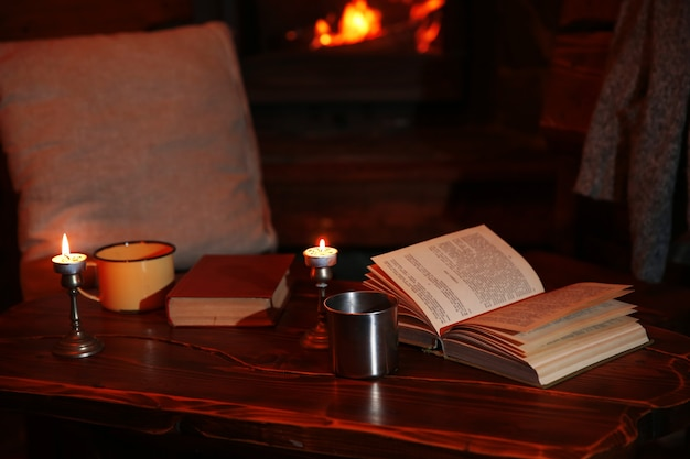 Hot tea or coffee in mug, book and candles on vintage wood table.