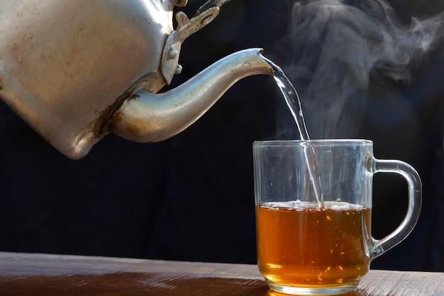 ホットティーカップはやかんで熱い蒸気を持っています。古い木製のテーブル、黒の背景に配置