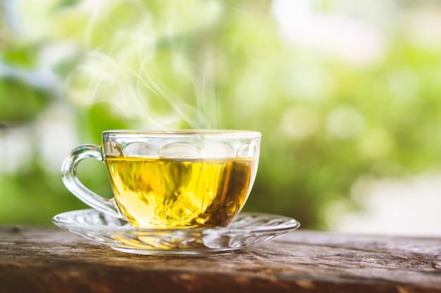 아침에 나무 테이블에 뜨거운 차 컵