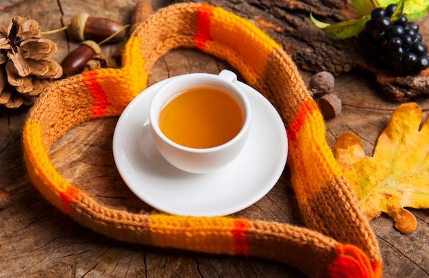 Hot tea cup with a scarf on wooden background