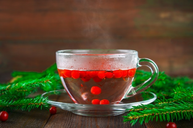 Hot tea from cranberries in a glass cup surrounded by fir branches on a wooden table.