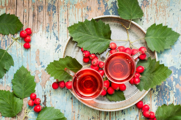 Hot tea from hawthorn berries in transparent glasses on woodtable top view