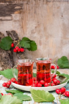 Hot tea from hawthorn berries in transparent glasses on woodtable