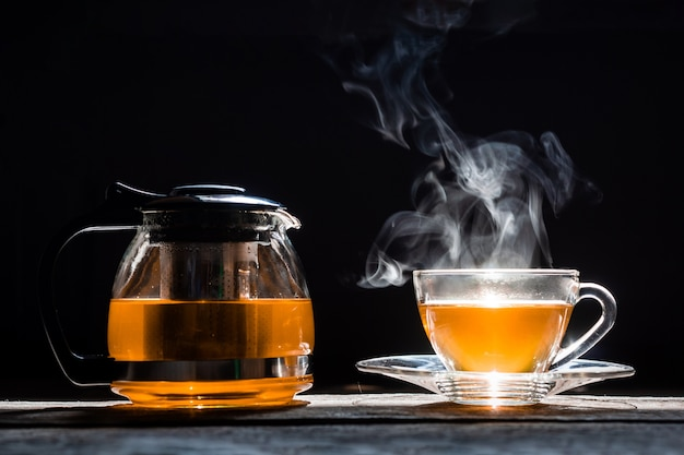 Hot tea in glass teapot and cup with steam on wood background