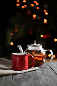 Hot tea  in a glass teapot next to a red mug decorated with an orange slice in the morning against a background of lights. sliced orange on a dark background.