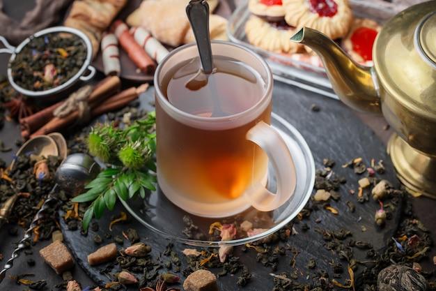 古い背景の上にカップで熱いお茶。