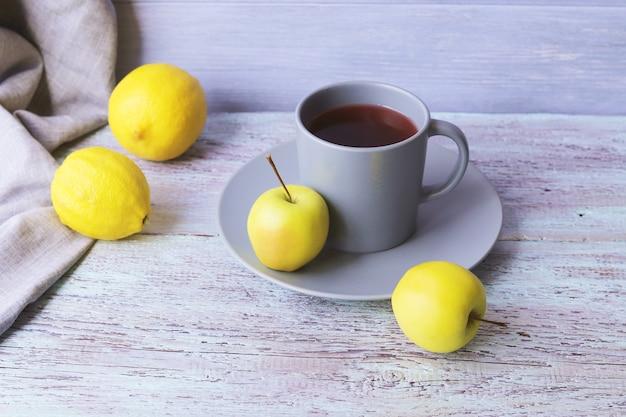 大きなカップに入った熱いお茶、木製のテーブルにレモンとリンゴ、黄色と灰色