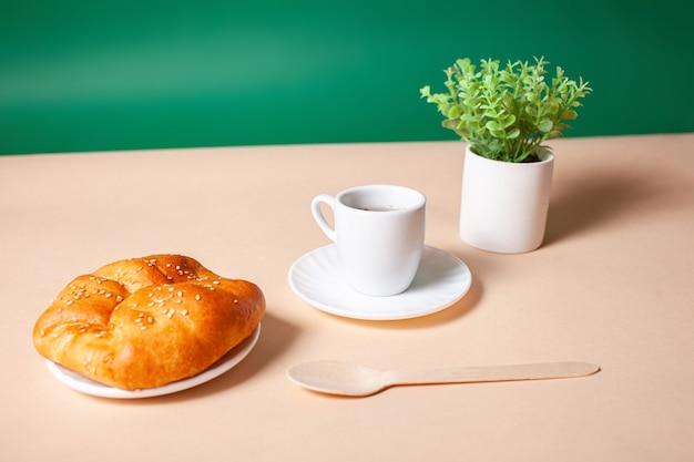 작은 컵에 뜨거운 차, 냄비에 식물, 접시에 롤빵, 친환경 나무 숟가락.