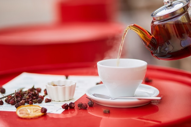 赤い背景の上のガラスのティーポットとカップの熱いお茶