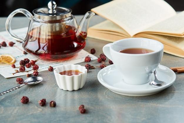 テーブルの上のガラスのティーポットとカップの熱いお茶