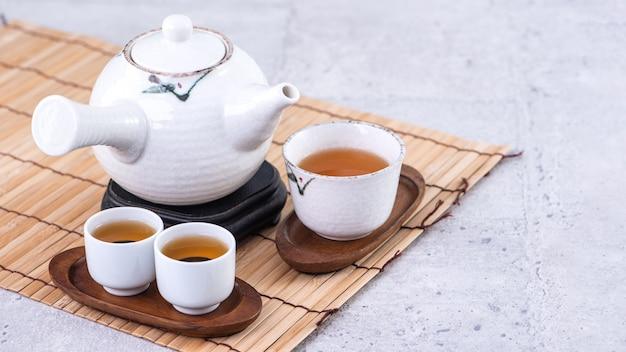 明るい灰色のセメントの背景、クローズアップ、コピースペースのデザインコンセプトの上のふるいに白いティーポットとカップの熱いお茶。