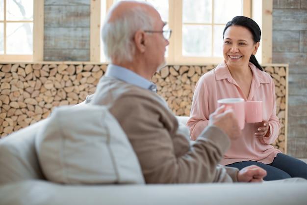 Горячий чай. радостный веселый воспитатель сплетничает со старшим мужчиной, улыбаясь и наслаждаясь чаем
