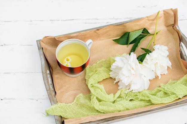 木製の白い背景の上の熱いお茶、天然ハーブティーの準備のための成分