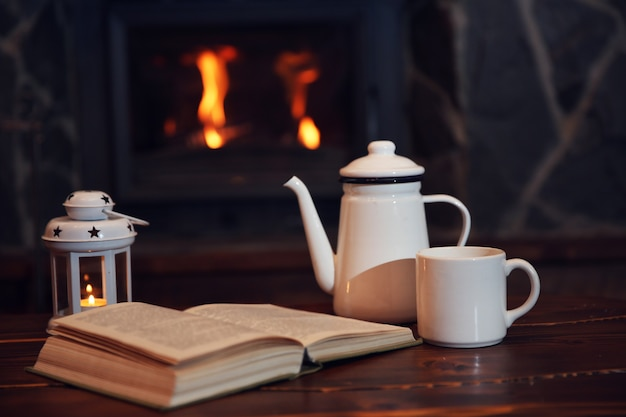 뜨거운 차 또는 커피 머그잔, 책 및 빈티지 나무 테이블에 촛불. 배경으로 벽난로