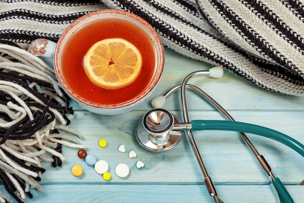 Hot tea, pills, knitted scarf and stethoscope