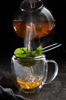 Горячий чай наливается в прозрачную кружку на черном фоне.