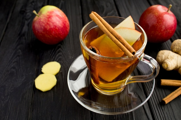 Hot tea with apples, cinnamon and ginger in the glass cup on the black