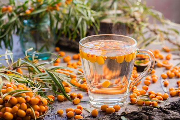 Hot tea with berries of sea-buckthorn in a glass