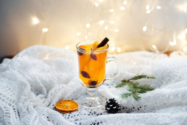 Hot tea with cinnamon, berries and oranges on a white wool blanket