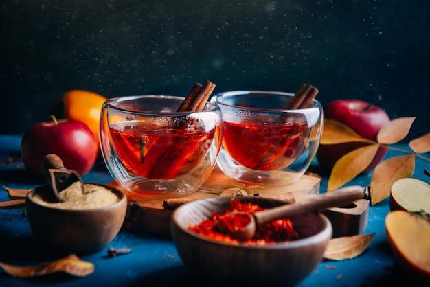 Hot tea with cinnamon sticks on blue
