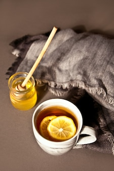 Hot tea with lemon and honey on the dark background