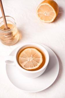 Hot tea with lemon and honey on the light background