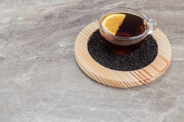 Горячий чай с лимоном на деревянной тарелке