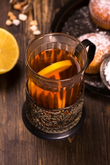 Hot tea with lemon slices in an old glass cup with vintage glass-holder