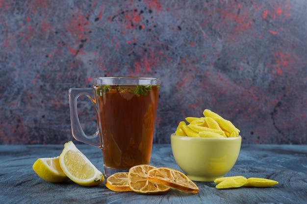 Горячий чай с лимонами и желтой миской желтых конфет на синем фоне.