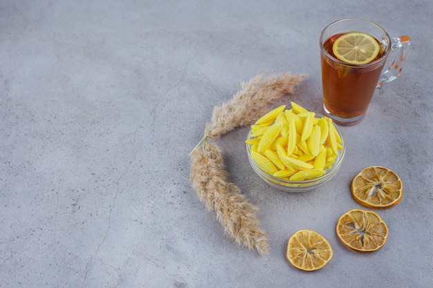 Hot tea with lemons and bowl of yellow sweet candies on stone background.
