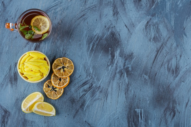 Hot tea with lemons and yellow bowl of yellow candies on blue background.