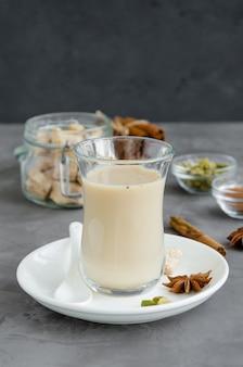 우유, 계피, 카 다몬, 아니스 및 기타 향신료와 함께 뜨거운 차, 어두운 배경에 유리에 인도 마살라 차. 수직, 복사 공간.