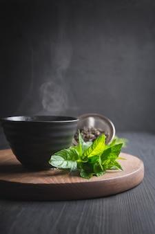 Горячий чай с мятой в черной чашке на темном