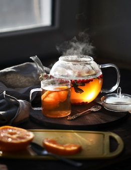 Hot tea with orange and berries in a glass teapot and in a  mug next to the window in the morning. sliced orange on a board on a dark background.