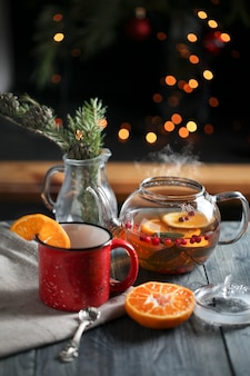 Hot tea with orange and berries in a glass teapot next to a red mug decorated with an orange slice in the morning against a background of lights. sliced orange on a dark background.