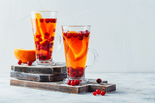 오렌지 슬라이스와 크랜베리 유리 높이 안경에 뜨거운 차. 겨울과 크리스마스를위한 뜨거운 음료. 텍스트 배치