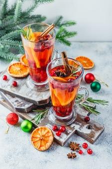 ガラスの背の高いグラスにオレンジスライスとクランベリーを入れたホットティー。冬とクリスマスのホットドリンク
