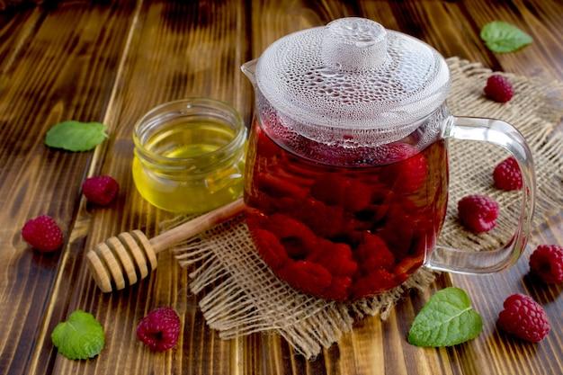 素朴な木製の背景にラズベリー、蜂蜜、ミントと熱いお茶。健康的な飲み物。