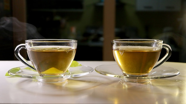 Hot tea with smoke in the glass cup with saucers. foods and drink concept.