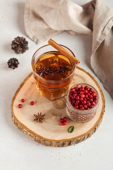 Hot tea with spices, apple and cranberry berries in a transparent glass mug on a wooden stand.