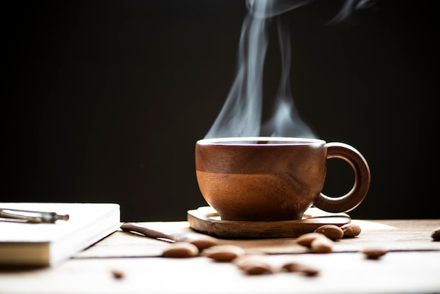 Hot tea with steam in wood cup and almonds on the wooden table.