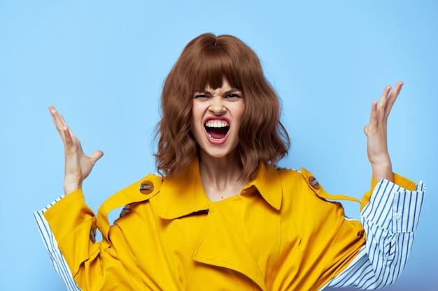 黄色いコートを着た温和な女性。手でジェスチャーをし、口をブルーに広げます。