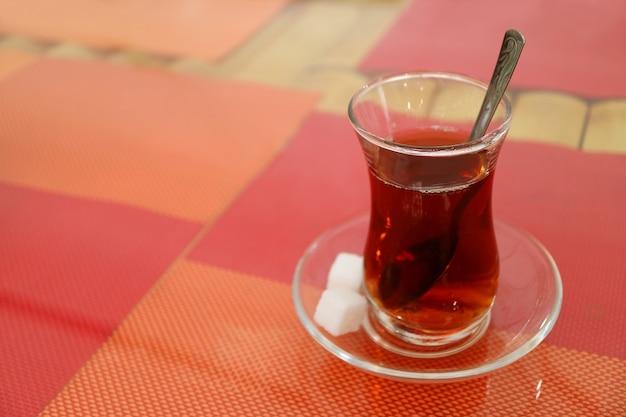 Горячий турецкий чай в стакане в форме тюльпана с сахарными кубиками, изолированные на красочных ковриках для завтрака